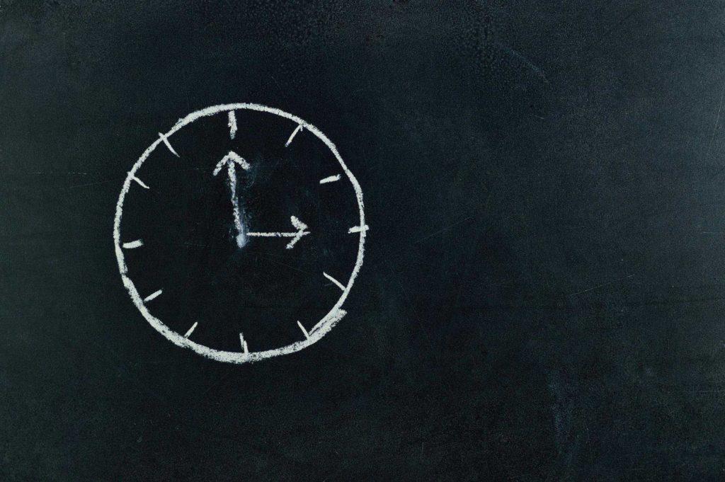 a clock drawn on a chalk board